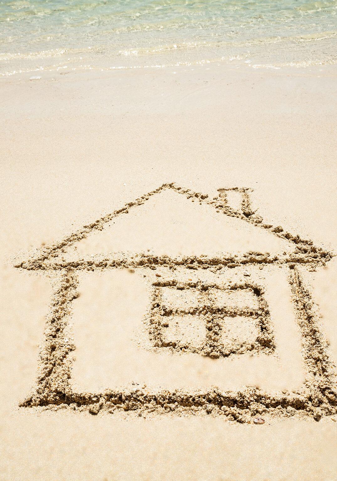 Close-up Of Hand Drawn House Near The Idyllic Sea On The Beach